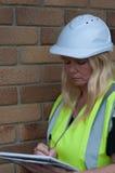 Kvinnabyggmästare som tar anmärkningar Arkivbild