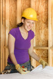 Kvinnabyggnadsarbetare som granskar arkitektoniska teckningar Royaltyfri Bild