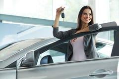 Kvinnachaufför Holding Car Keys Bilvisningslokal Fotografering för Bildbyråer