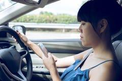 Kvinnachaufför som använder en smart telefon Arkivbild