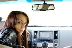 Kvinnachaufför som ser in i den bakre platsen arkivfoton