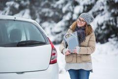 Kvinnachaufföranseende bredvid bilen och håll bensindunken arkivfoto