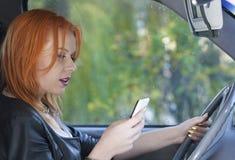 Kvinnachaufför som överför sms på telefonen, medan köra Royaltyfri Bild