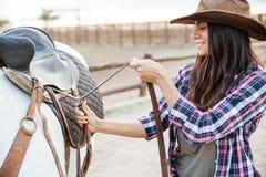 Kvinnacowgirlanseende och sättasadel på häst royaltyfria bilder