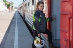 Kvinnacyklist som får det intercity drevet med den vita hjälmen i händer och det iklädda motorcykelomslaget, copyspace Royaltyfri Foto
