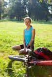 Kvinnacyklisten som tycker om, kopplar av fjädrar in parkerar Royaltyfria Bilder