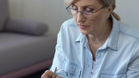 Kvinnadanandeanmärkningar i notepaden som hör försiktigt online-grupper, själv-utveckling lager videofilmer