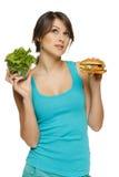Kvinnadanandebeslut mellan sund sallad och snabbmat Royaltyfri Fotografi
