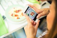 Kvinnadanandefoto av mat på smartphonen royaltyfri bild