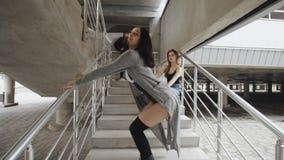 Kvinnadansen och utför modern höft-flygtur eller modedansen på konkret trappa, kvinnligt posera för dansare stock video