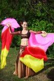 Kvinnadanser med skyler ventilatorer Arkivbild
