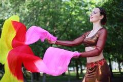 Kvinnadanser med skyler ventilatorer Arkivbilder
