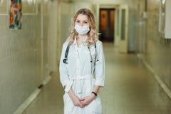 Kvinnadoktor i ett vitt lag i korridoren arkivbild
