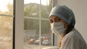 Kvinnadoktor i medicinsk maskering mot fönstret stock video