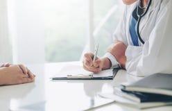 Kvinnadoktor och kvinnlig patient i sjukhuskontor arkivbilder