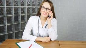 Kvinnadoktor Sitting på hennes kontor och användasmartphone stock video