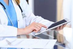 Kvinnadoktor som använder minnestavladatoren, medan sitta på skrivbordet i sjukhuskontoret, closeup Sjukvård försäkring royaltyfri foto