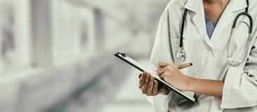 Kvinnadoktor som arbetar p? sjukhuskontoret arkivbild