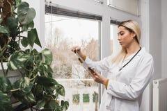 Kvinnadoktor som kontrollerar höftfilmröntgenstrålen royaltyfria bilder
