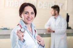 Kvinnadoktor som rymmer en stetoskop i vårdcentral Royaltyfria Bilder