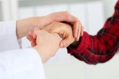 Kvinnadoktorn räcker det hållande kvinnliga barnet den tålmodiga handen arkivfoto