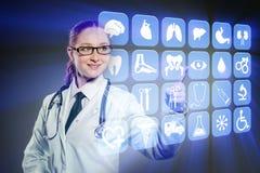 Kvinnadoktorn som trycker på knappar med olika medicinska symboler Royaltyfri Bild