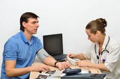 Kvinnadoktorsinstrumentet för att mäta tryck behandlar en patient en man royaltyfri foto