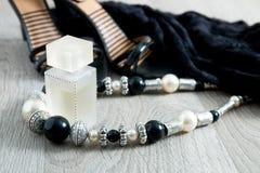 Kvinnadräkt Svart snör åt klänningen, skosandaler, halsbandet och doft på grå träbakgrund Aftontillbehör för parti Arkivfoto