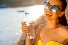 Kvinnadricksvatten från den genomskinliga flaskan på Arkivfoto