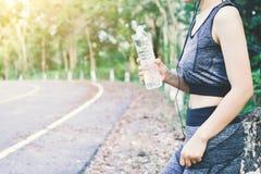 Kvinnadricksvatten i trädbakgrund royaltyfria bilder