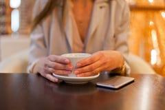 Kvinnadrinkcoffe i kafé Royaltyfria Bilder