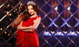 Kvinnadrottningprinsessan i kronan och luxklänningen, ljus festar backgr arkivfoton