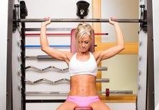 Kvinnaelevatorhantlar i sportmitten som framkallar muskler Royaltyfria Bilder