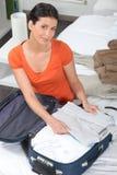 Kvinnaemballage henne kläder in i en resväska Arkivfoto