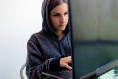 Kvinnaen hackerprogrammerare arbetar på datoren i cybersäkerhetsmitten som fylls med skärmskärmar royaltyfria foton