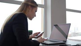 Kvinnaentreprenör som använder smartphonen och bärbara datorn på arbetstabellen i affärskontor arkivfilmer