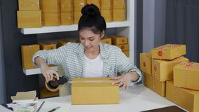 Kvinnaförbereder online-entreprenören som använder bandet till det packande hemmastadda kontoret för jordlottasken, produkten för arkivfilmer