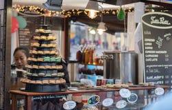 Kvinnaförsäljningar godis och drinkar på jul marknadsför Royaltyfria Bilder