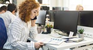 Kvinnaförsäljningschef som talar på mobiltelefonen och läser grafer royaltyfri foto