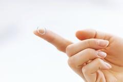 Kvinnafinger med kontaktögat Lens band för mått för äpplebegreppshälsa Royaltyfria Foton