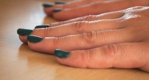 Kvinnafingrar med gräsplan spikar polermedel royaltyfri fotografi