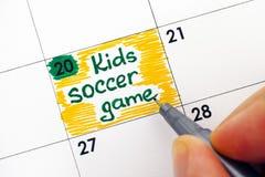 Kvinnafingrar som skriver påminnelse, lurar fotbollleken i kalender fotografering för bildbyråer
