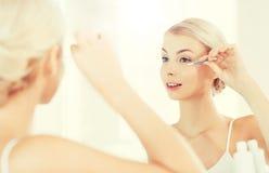 Kvinnafixandemakeup med bomullsbomullstoppen på badrummet Royaltyfria Bilder