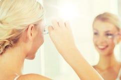 Kvinnafixandemakeup med bomullsbomullstoppen på badrummet Fotografering för Bildbyråer