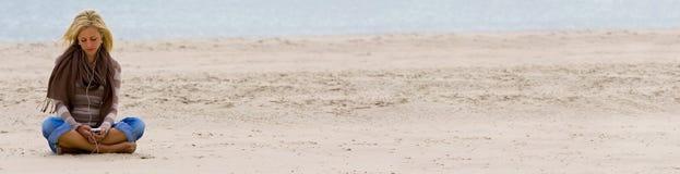 Kvinnaflicka på stranden som lyssnar till musik på den smarta telefonen arkivfoton