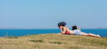 Kvinnaflicka som ligger på gräsläseboken royaltyfri fotografi
