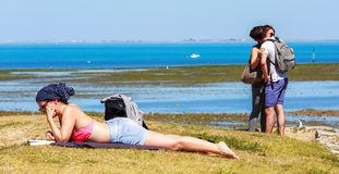 Kvinnaflicka som ligger på gräsläseboken och vänner arkivbild
