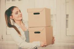 Kvinnaflyttning in i bärande askar för lägenhethus Royaltyfri Fotografi