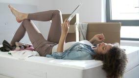 Kvinnaflyttning in i nytt hem genom att använda den Digital minnestavlan som ligger på säng arkivfilmer