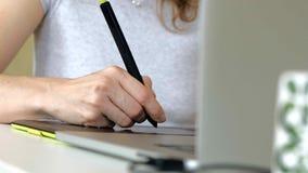 Kvinnaformgivareattraktioner på en diagramminnestavla Kvinna som i regeringsställning arbetar med den hemmastadda bärbara datorn arkivfilmer